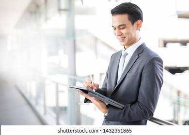 Young Asian business man smile using a tablet