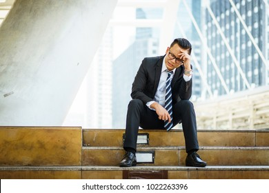 Young Asian business man suffering head pain or migraine at the walkway in the city after his work. Portrait of tired young business man, stress, crisis, depression, failure in business concepts.