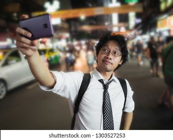 Young Asian business man taking a picture or selfie in the street at night. Social and internet of thing concept.