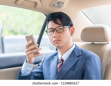 Young asian business men portrait in suit  talking on the phone in car