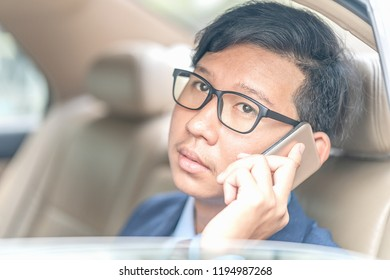 Young asian business men portrait in suit working in the backseat of a car