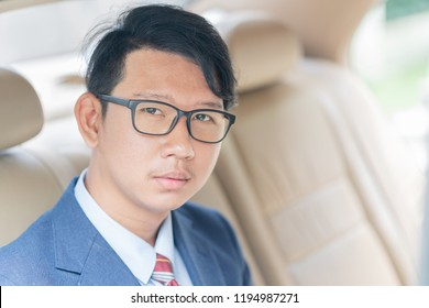 Young asian business men portrait in suit sit in the backseat of a car