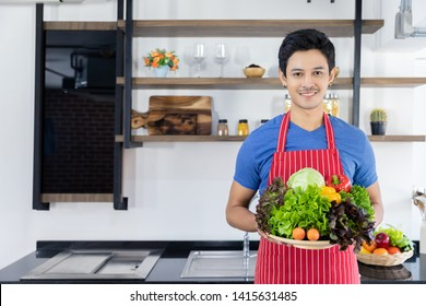 Young Asian business owner of restaurant, diner, cafe is smiling and holding vegetable basket which preparing to make healthy diet food in kitchen room. Chef feels happy to service and he love his job