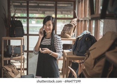 young asian business owner talking to mobile phone in her fashion store