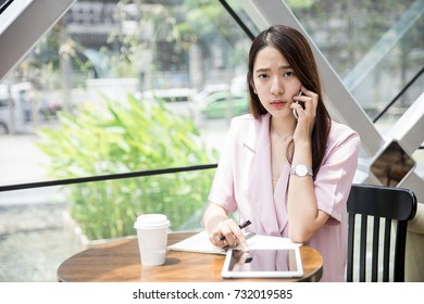 Young Asian business owner talking to her client