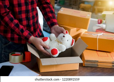 Young asian business owner working online shopping small business with cardboard box at work.Seller prepares the delivery box for the customer,online sales,ecommerce,writing order of product orders.