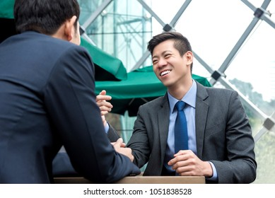Young Asian business partners happily talking at cafe