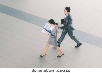 Young Asian business people with documents hurrying to work