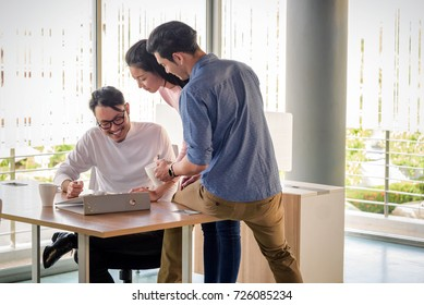 young asian business people, man and woman, working with team in startup office