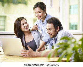 young asian business people team working together in office using laptop computer.