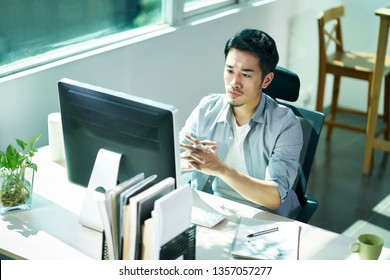 young asian business person sitting in office thinking while looking at monitor of desktop computer.