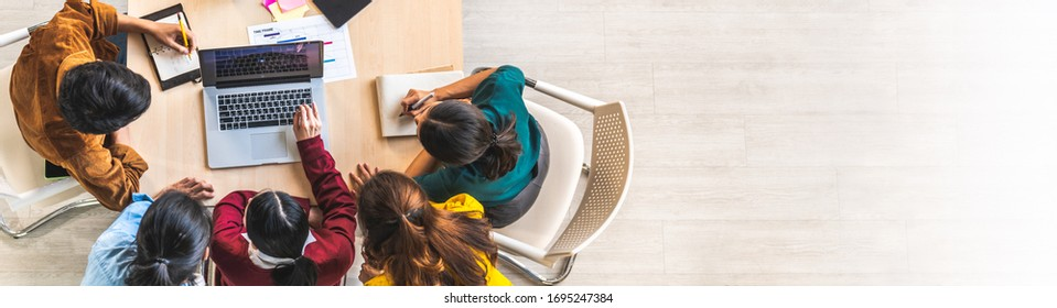 Young Asian business team work together in project brainstorm meeting, using laptop computer. Colleague coworker, startup office or people teamwork concept. Top view, banner size with copy space - Shutterstock ID 1695247384