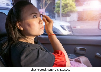 Young asian business woman doing makeup in car to drawing eyebrow before arrived her office while the car is on the way, Emotion of rush in time with people and lifestyle in the city concept