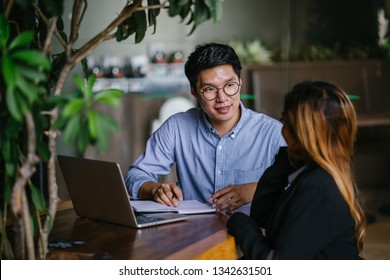 A young Asian business woman during a consultation with a young Korean Asian man for business advice. They are sitting in a trendy coworking space during the day and having a business discussion.