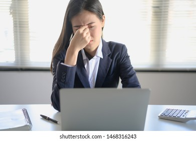 Young Asian business woman felling tired and have an eye pain after work with computer monitor for a long time in an office.