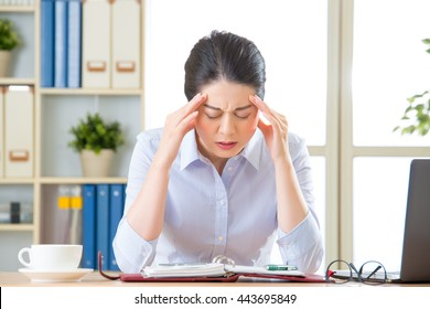 Young asian business woman with headache in office