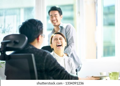 young asian business woman lets out a big laughter while discussing business with two teammates