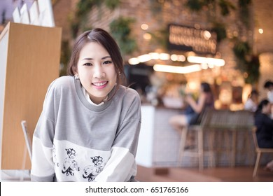 Young Asian business woman looking to the camera with relaxing pose