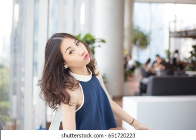 Young Asian business woman posing with cheeky, naughty or sassy emotion to camera