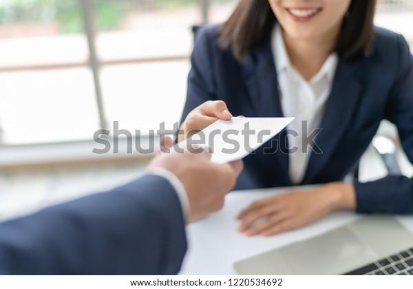 Junge asiatische Geschäftsfrau, die von Chef oder Geschäftsführer im Büro Lohn- oder Bonusgeld erhält.