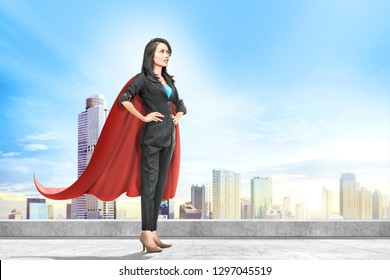 Young asian business woman with red cape standing on the rooftop with cityscapes background