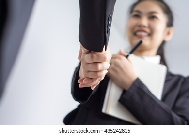Young asian business woman shaking hands on white background, Indoors