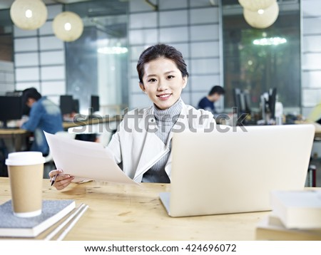 young asian business woman sitting at desk in office holding document looking at camera.