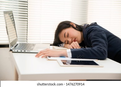 Young Asian business woman Sleep on table in office because overworking , stressed from work overload and is a tired and sleepy lady.