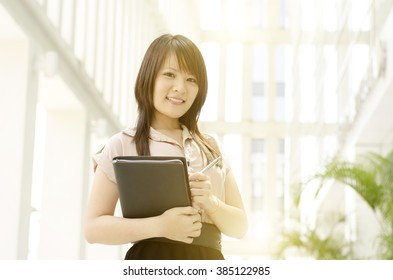 Young Asian business woman smiling and holding file folder, standing in an office environment, beautiful golden sunlight background.