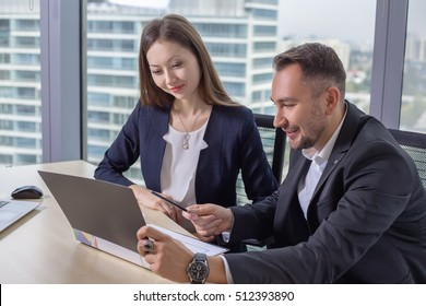 Young asian business woman in suit discusses the report with his colleague male at work in office