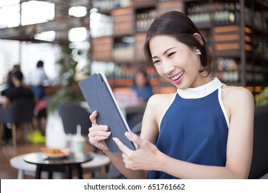 Young Asian business woman surprising while looking to tablet after checking her profit income or stock trading