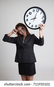 Young Asian business woman thumbs down with a clock on gray background