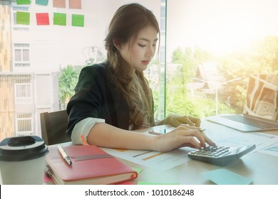 Young asian business woman using calculator on wooden desk in office. Business portrait concept.