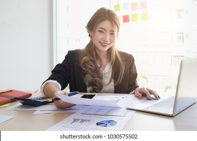 Young asian business woman using laptop computer and cell phone for contact customer on wooden desk in office. Business portrait concept.