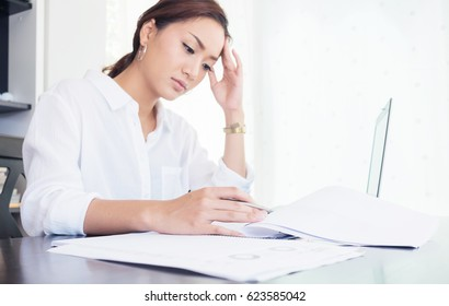 young Asian business woman worried in reading and analysis data financial report at home