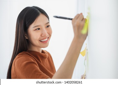 Young Asian business woman writing on sticky note for reminder list and pending works