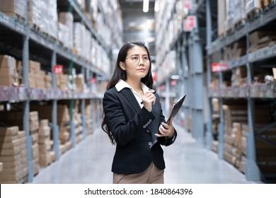 Junge asiatische Arbeiter, Eigentümer, Unternehmerin, die eine Datei hält, die über dem Regal nach oben schaut mit efulfillment Service Business Warehouse Online-Konzept. asiatische Waren.