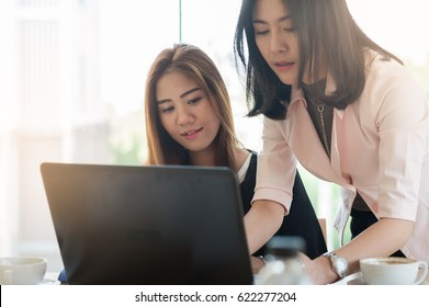 Young Asian business workers working together with laptop computer in office. Business startup teamwork and brainstorm concept