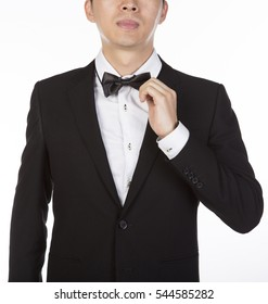 young asian businessman adjusting white bow tie, isolated white background