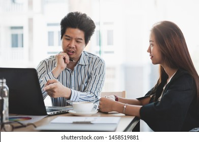 Young Asian businessman and businesswoman talking about their work while looking at laptop monitor in meeting room. Startup business for freelance workers concept