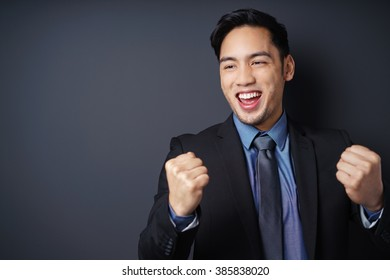 Young Asian businessman cheering in jubilation raising his fists in the air as he celebrates his success