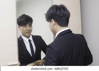 Young asian businessman doing up his tie knot in a mirror.