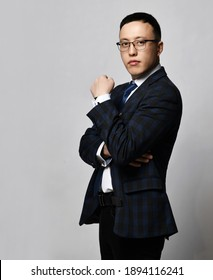 Young asian businessman expert in jacket, tie and glasses stands side to camera with arms crossed at chest making statement giving an expert assessment. Business, office worker, stylish official look