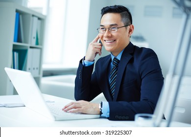 Young Asian businessman in eyeglasses calling in office