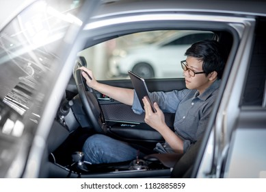 Young Asian businessman with glasses reading news on digital tablet while sitting on driver seat in his car. Business and technology concept