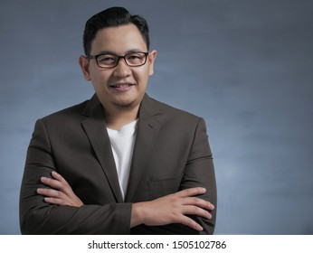 Young Asian businessman with glasses wearing white shirt and blazer, smiling looking at a camera, crossed arm