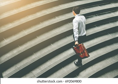 Young Asian businessman holding Brown leather bag  working on  staircase go office hurry work time with sunset top view and vintage tone