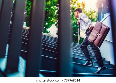 Young Asian businessman holding Brown leather bag working on staircase go office hurry work time with sunset top view and  instagram style filter photo vintage tone