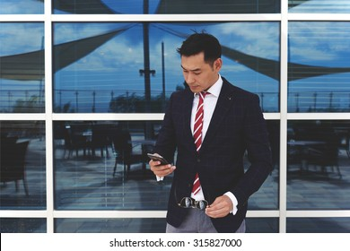 Young asian businessman holding his mobile phone while standing at office building window outdoors, successful man entrepreneur dressed in stylish luxury clothes using cell telephone during work break