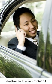 A young asian businessman making a business call in the back of a car
